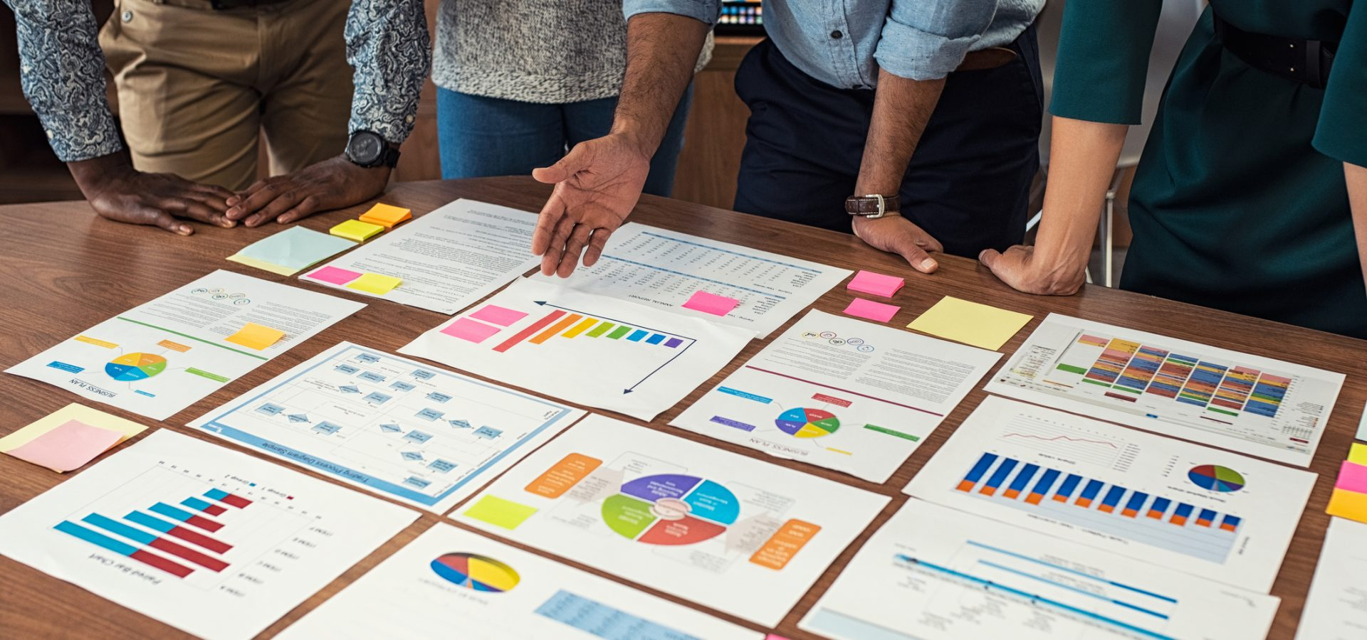 Financial and business documents on table with multiethnic hands working on it. Latin business manager with colleagues working on new startup project. Closeup business man and businesswoman hands understanding pie and bar graphs during meeting.